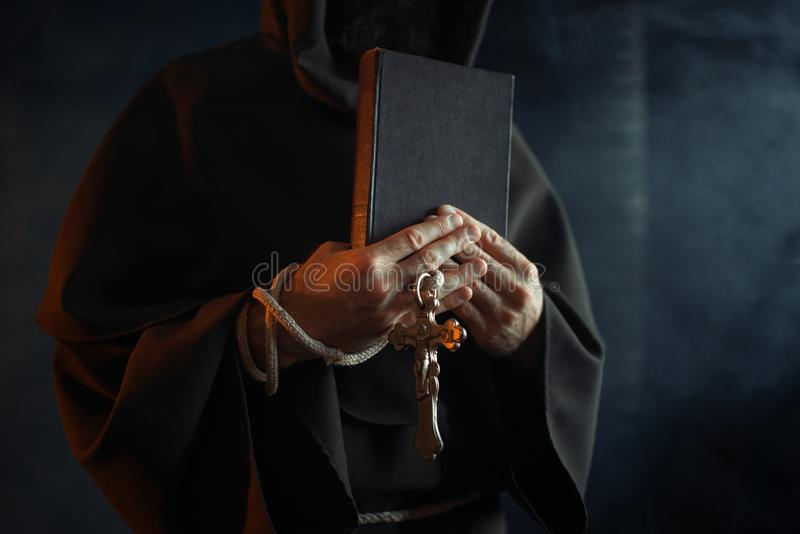 Medieval monk holds book and wooden cross in hands. Black background, secret ritual. Mysterious friar in dark cape. Mystery and spirituality royalty free stock photos