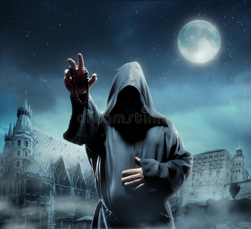 Medieval monk at night. Medieval monk against church at night stock photo