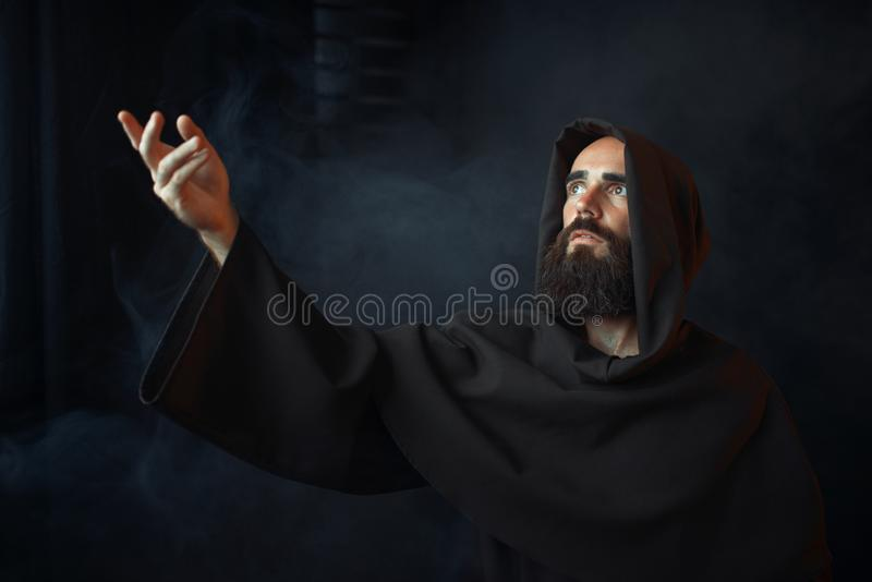 Medieval monk praying against a window with light. Medieval monk praying against a window with bright light, religion. Mysterious friar in dark cape, Mystery and stock photo