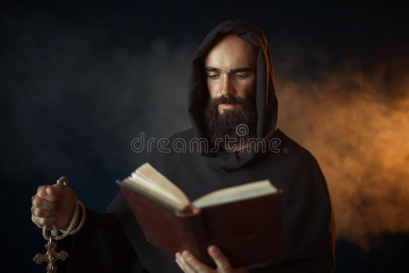 Medieval monk praying with book in church. Medieval monk praying with book in hands in church, secret ritual. Mysterious friar in dark cape. Mystery and royalty free stock photos