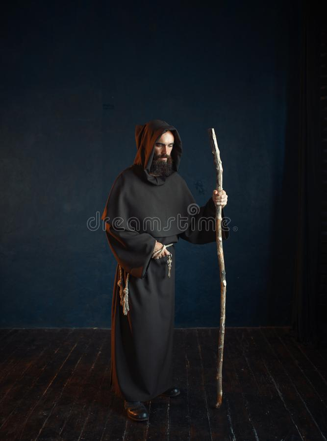 Medieval monk in robe with hood rests on a stick. Medieval monk in black robe with hood rests on a stick, religion. Mysterious friar in dark cape royalty free stock photo