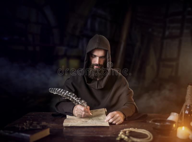 Medieval monk in robe writes with a goose feather. Medieval monk in robe and hood writes with a goose feather, black background, secret ritual. Mysterious friar royalty free stock photo