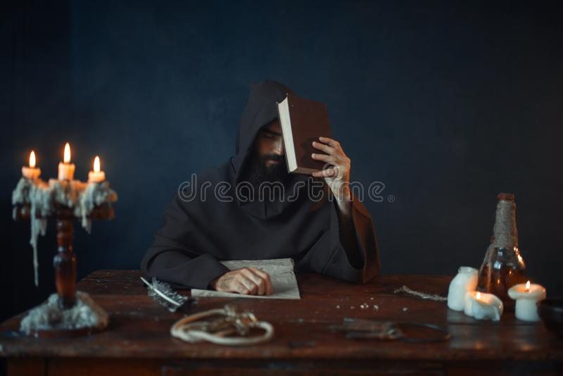 Medieval monk sitting at the table and reads. Secret scripture. Mysterious friar in dark cape. Mystery and spirituality stock photo