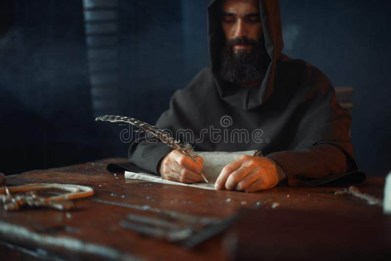 Medieval monk sitting at table and write, top view. Medieval monk sitting at the table and writes with a goose feather, top view, secret scripture. Mysterious royalty free stock images