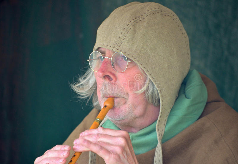 Medieval musician or minstrel playing whistle. stock image