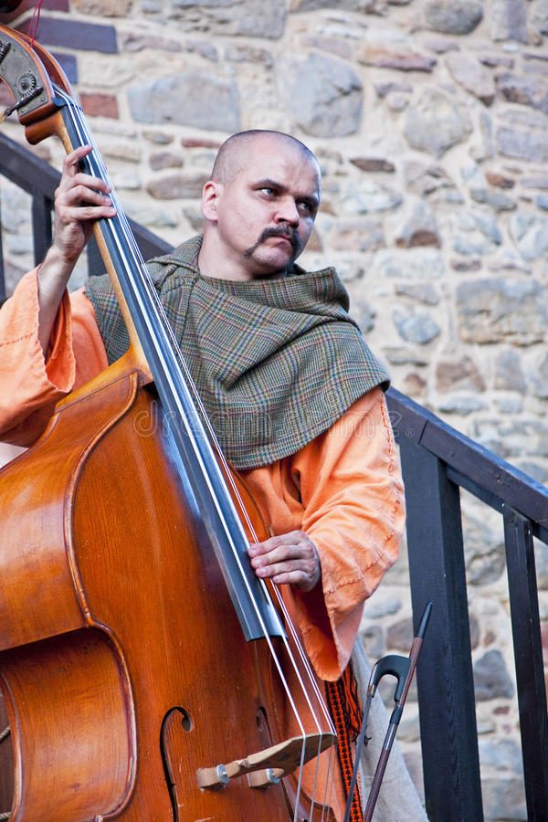 Medieval musician playing the big old double bass stock photos