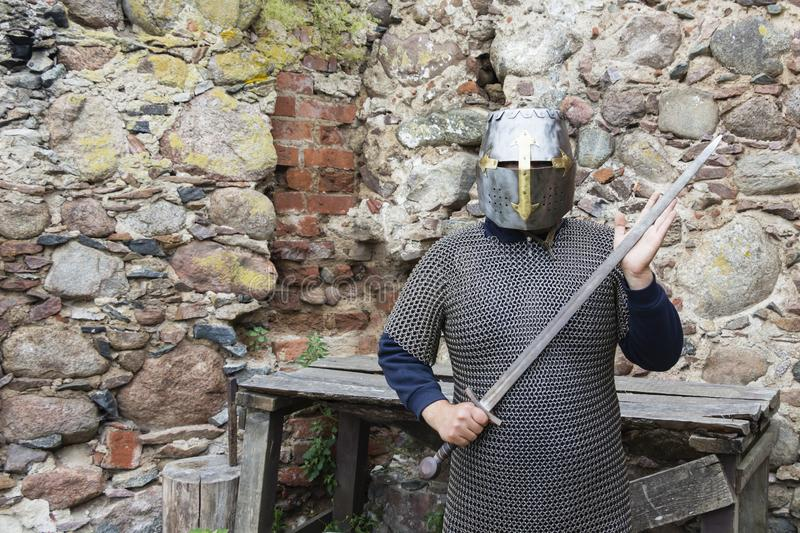 Medieval old knight helmet and chain mail for protection in battle. Very heavy headdress on stand in nature. Middle ages armor con stock photo