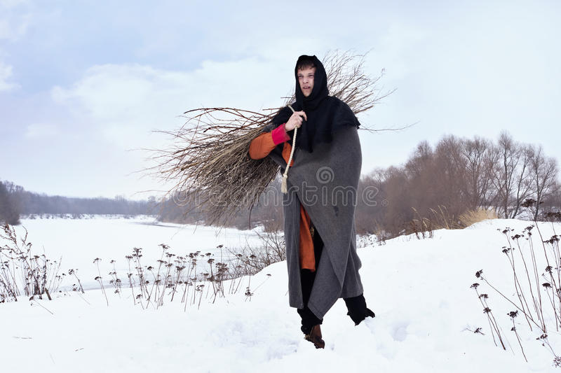 Medieval peasant with a firewood bundle royalty free stock images