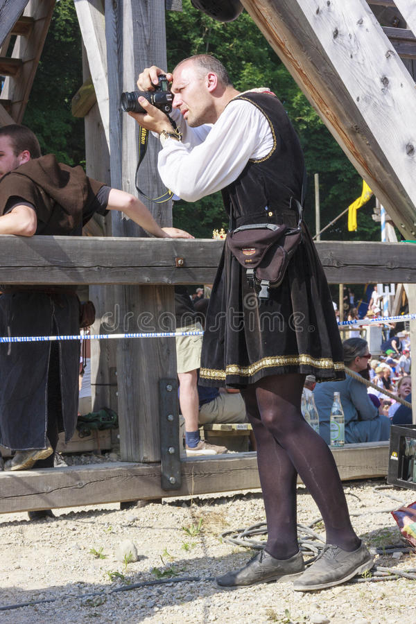 Medieval photographer. KALTENGER, 2010 Jul 11 - A medieval photographer standing among the crowd looking in the viewfinder of his camera capturing picture