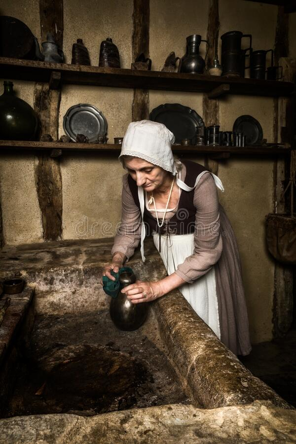 Medieval portrait of a maid cleaning in kitchen royalty free stock photography
