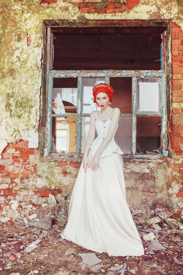 Medieval redhead princess with hairstyle in corset. Baroque era queen with magic hairdo against stone wall. Rococo era. Medieval. Princess in historic palace royalty free stock photography