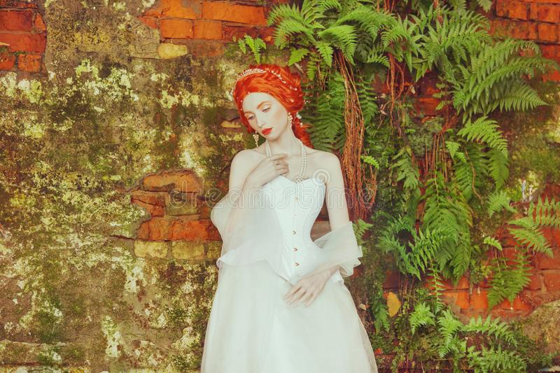 Medieval redhead princess with hairstyle in corset. Fairy tale queen with magic hairdo against stone wall. Fairytale doll. Medieva royalty free stock image