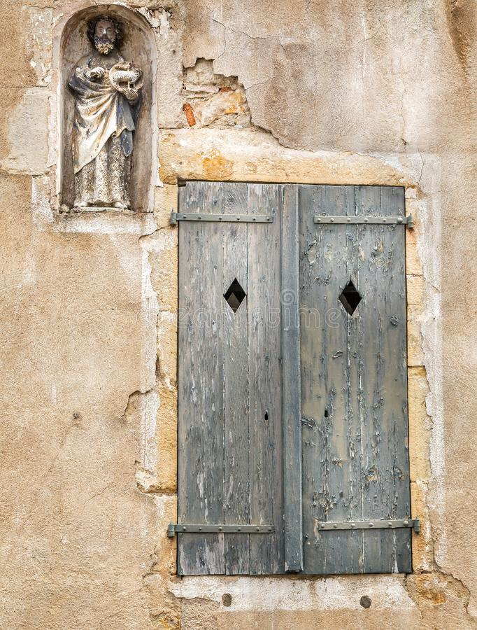 Medieval religious statue in wall alcove and weathered wooden shutters in Semur en Auxois, France royalty free stock images