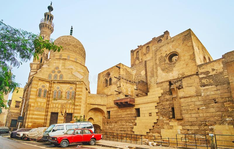 The ruins of Khayrbak Mosque, Cairo, Egypt. The medieval ruins of Amir Khayrbak Funerary Complex with shabby walls, richly decorated dome and minaret, Cairo royalty free stock images