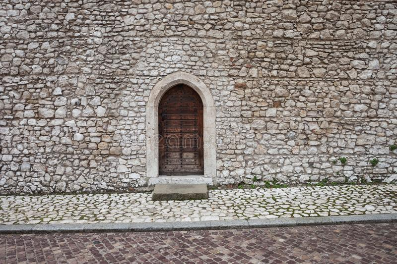 Medieval Stone Castle Wall With Door. Medieval castle stone wall with arched wooden door and sidewalk stock photo