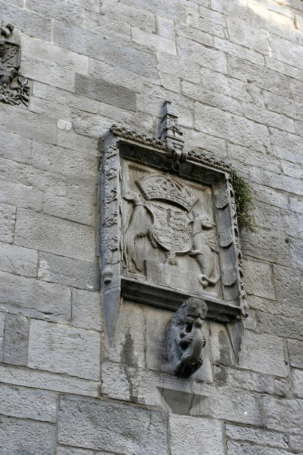 The medieval stone relief with the fantastic animals and the emblem on the stone wall of the medieval building. The medieval stone relief with the fantastic stock photos