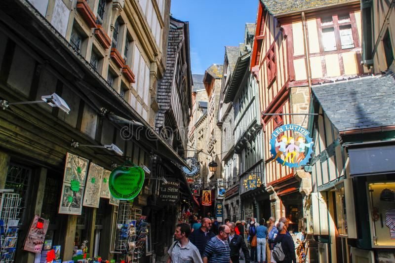 Medieval stone stone street with stone houses with cafes, restaurants and souvenir shops and people walking along it royalty free stock image
