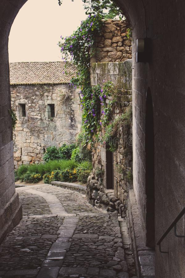 Medieval street arch in provence. Ancient european architecture. Charming brick castle gate with flowers and plants and lantern. Romantic travel concept. Old royalty free stock photos