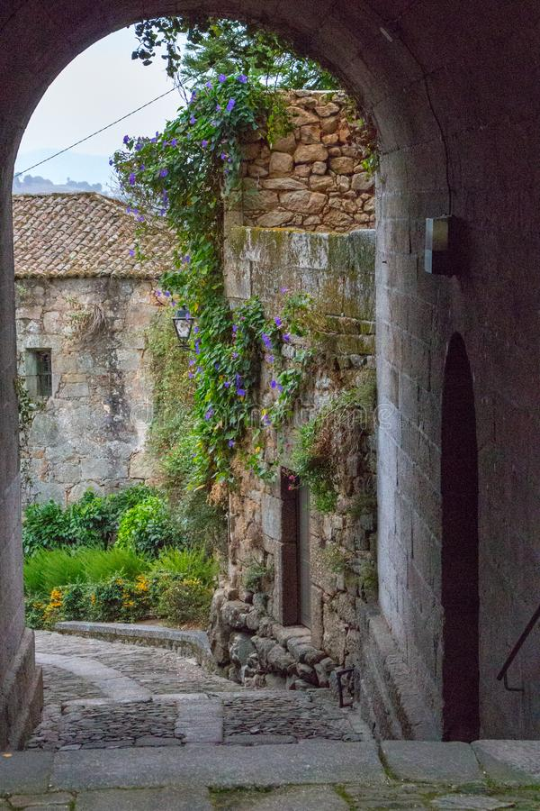 Medieval street arch in provence. Ancient european architecture. Charming brick castle gate with flowers and plants and lantern. Romantic travel concept. Old royalty free stock photography