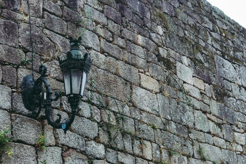 Medieval street lamp on old brick wall colored. Facade of ancient buiding, Europe. Grunge outdoor design. Old castle wall. Grunge stone wall textured royalty free stock images
