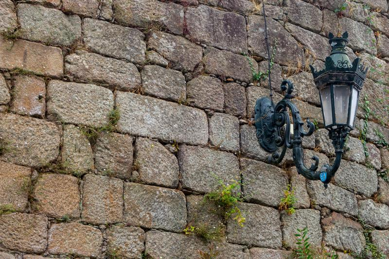 Medieval street lamp on old brick wall colored. Facade of ancient buiding, Europe. Grunge outdoor design. Old castle wall. Grunge stone wall textured stock photo