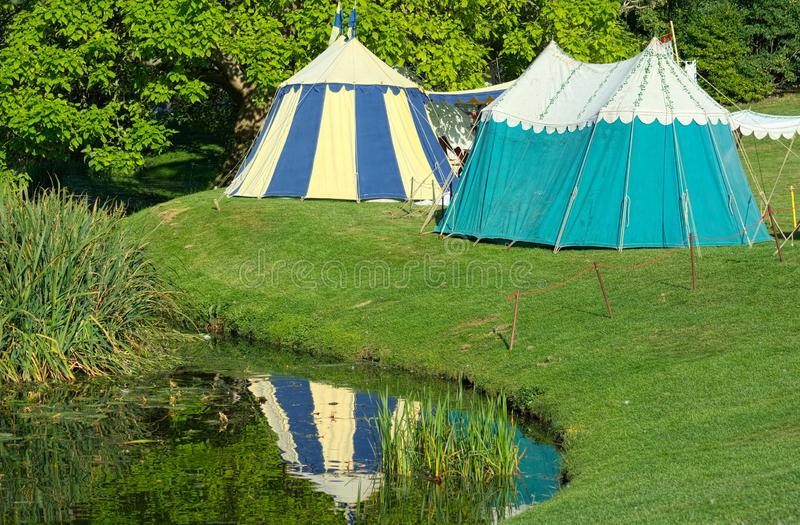 Medieval tents reflected in pond. Tudor reenactment. Medieval village tents erected near a pond as part of a Tudor period reenactment living history event royalty free stock images