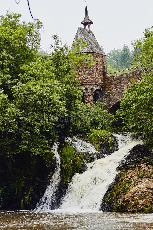 Medieval tower, bridge and waterfall. Old medieval tower and bridge, small waterfall and green trees royalty free stock photos