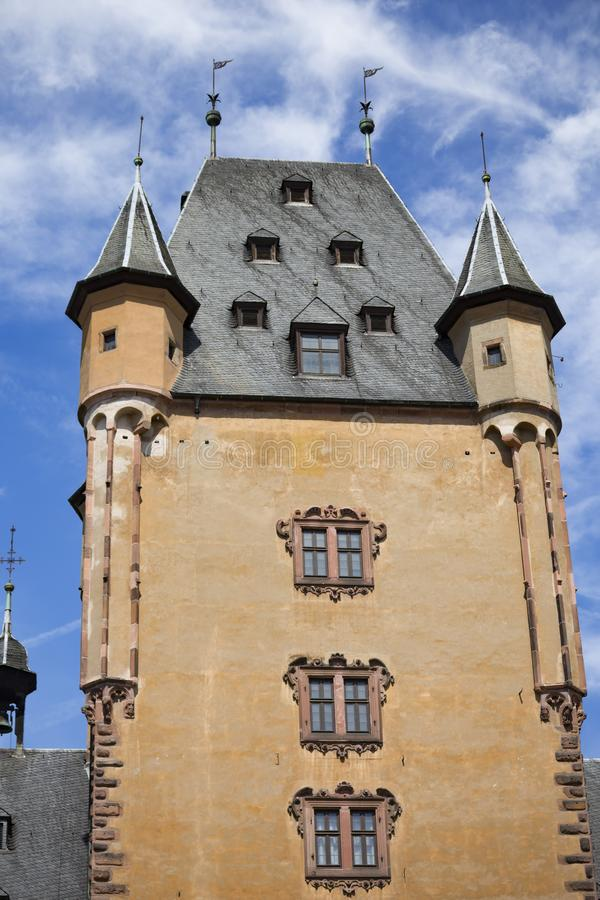 Medieval tower. Castle Johannisburg, town Aschaffenburg, Germany. Fabulous medieval tower of castle close-up  against  blue cloudy sky. Ancient Schloss royalty free stock image