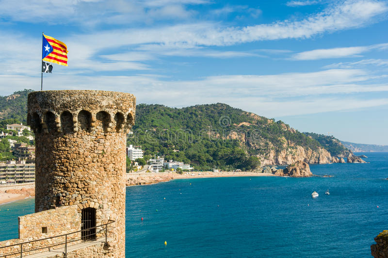 Medieval tower with catalonia's flag. Catalonia's flag on the top of the medieval tower in Tossa de Mar stock photo