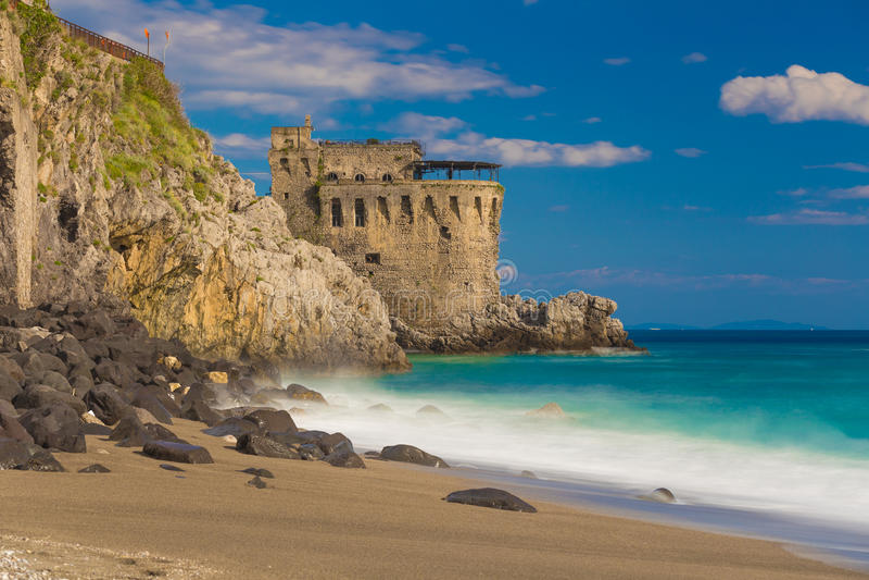 Medieval tower on the coast of Maiori town, Amalfi coast, Campania region, Italy. Medieval tower on the coast of Maiori town, blurred sea waves effect, Amalfi stock photography