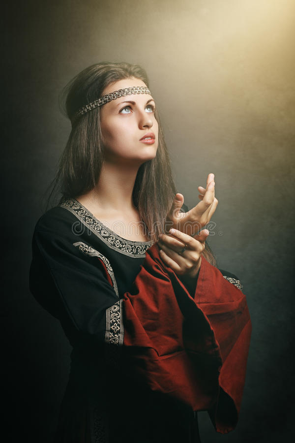 Medieval woman with eyes to soft holy light royalty free stock photos