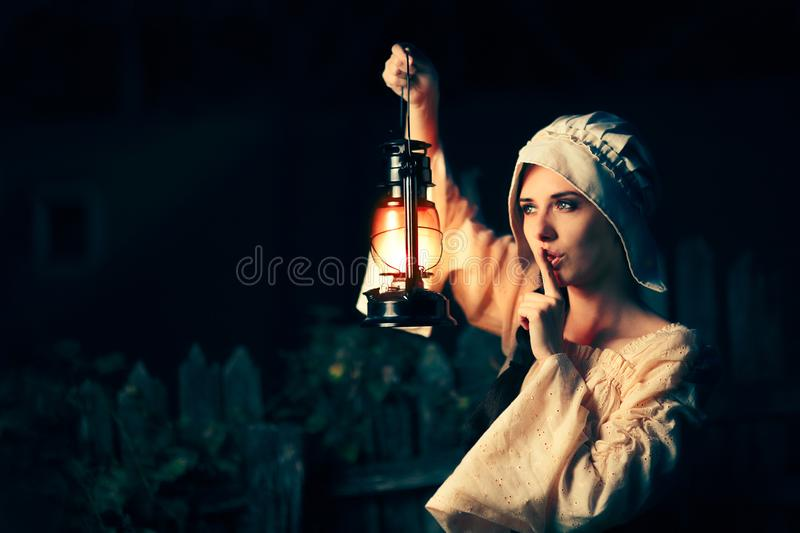 Medieval Woman with the Finger on the Lips Holding a Lamp royalty free stock photography