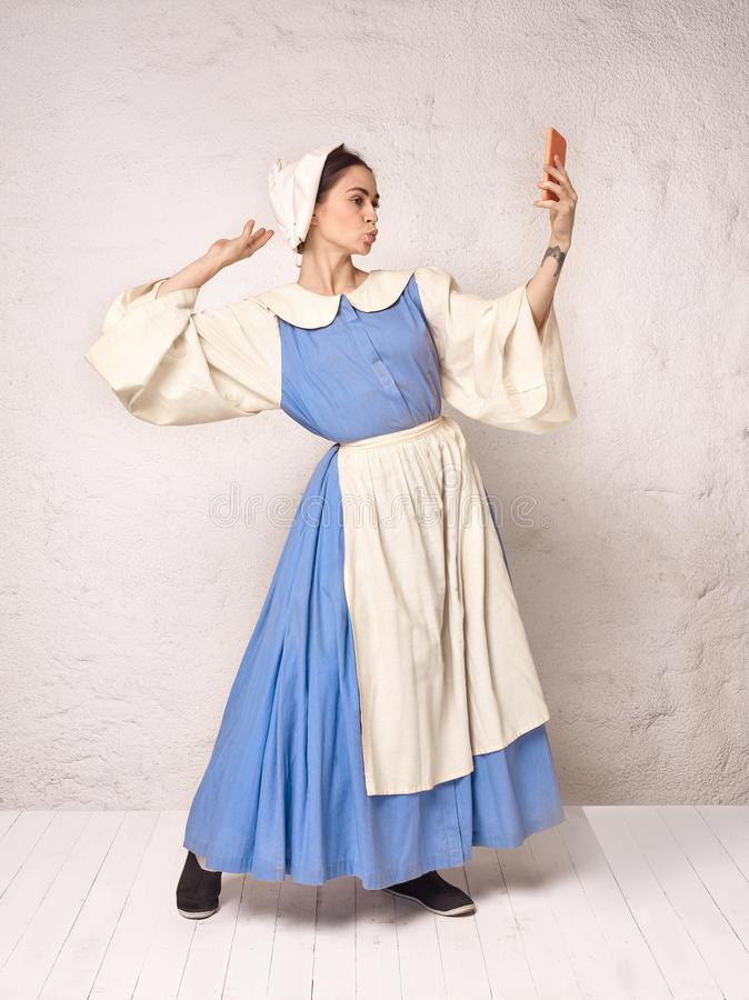 Medieval Woman in Historical Costume Wearing Corset Dress and Bonnet. Beautiful peasant girl wearing thrush costume with mobile phone royalty free stock photo