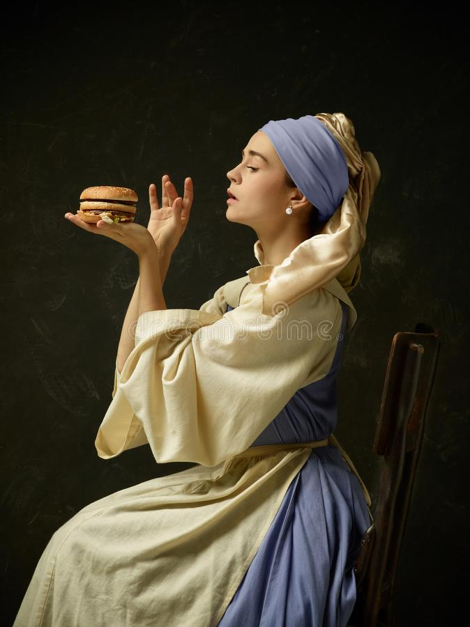 Medieval Woman in Historical Costume Wearing Corset Dress and Bonnet. Medieval Woman in Historical Costume Wearing Corset Dress and Bonnet with burger stock photo