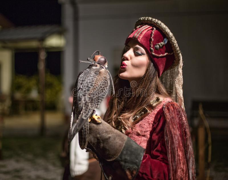 Medieval woman holding a falcon on his arm royalty free stock photography