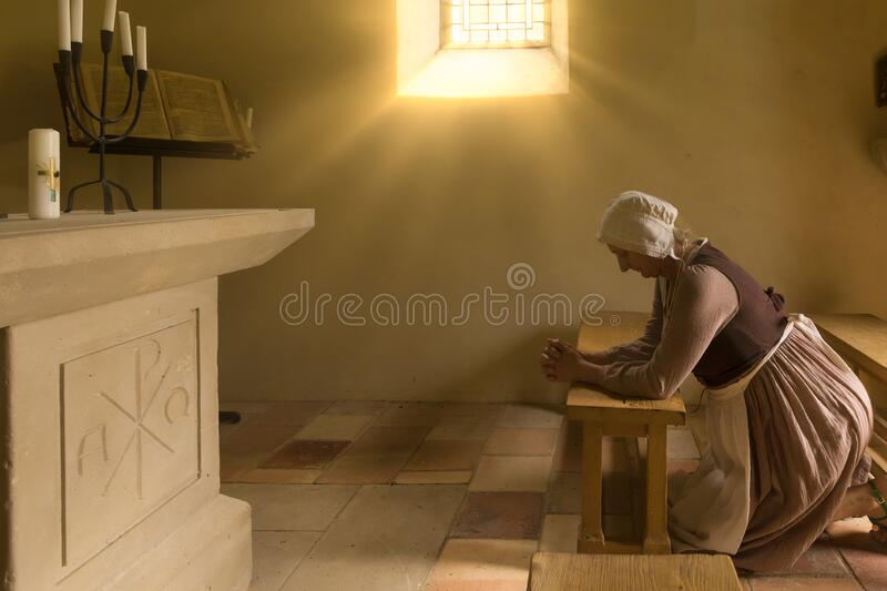 Medieval woman kneeling in prayer stock photography