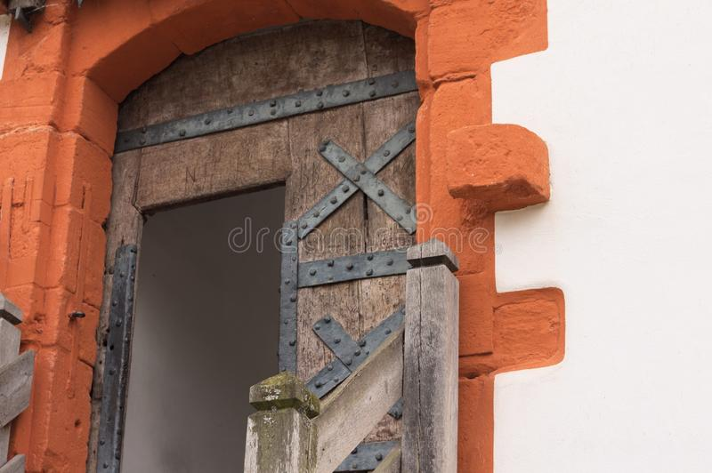 Medieval wooden door of a castle with red decorations royalty free stock photo