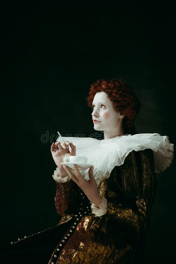 Medieval young woman as a duchess. Medieval redhead young woman in golden vintage clothing as a duchess holding a cigarette and a cup of coffee on dark green stock photos
