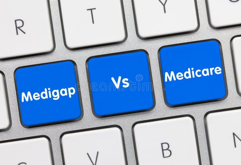 Medigap Vs Medicare - Iscrizione sulla tastiera blu fotografie stock