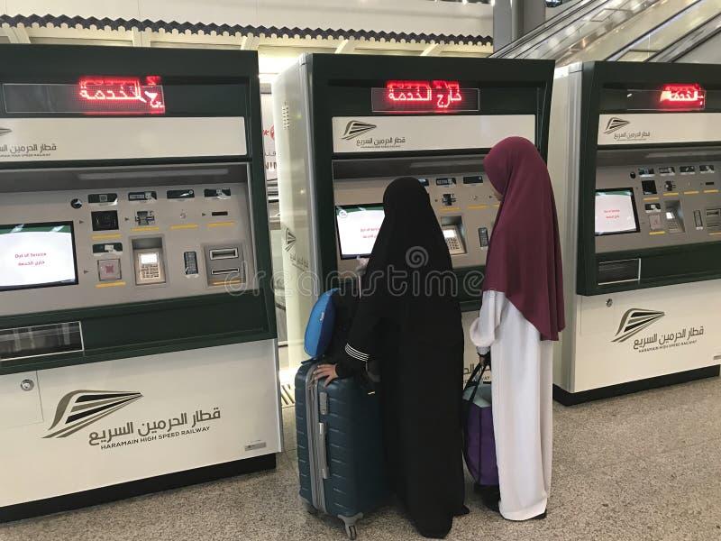 MEDINA, САУДОВСКАЯ АРАВИЯ - 27-ОЕ МАЯ 2019: 2 неопознанных мусульманских дамы смотрят новую автоматизированную машину билета расп стоковые фотографии rf