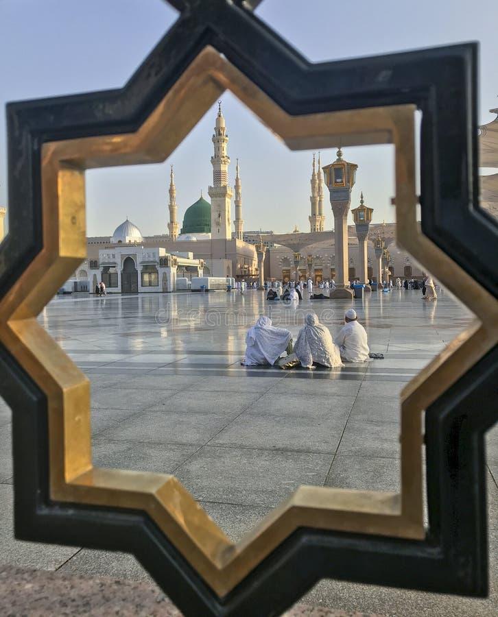MEDINA, KONINKRIJK VAN SAOEDI-ARABISCHE ARABIË-CIRCA MEI 2019: de door-de-poortmening van Moslims rust bij de samenstelling van M royalty-vrije stock foto's
