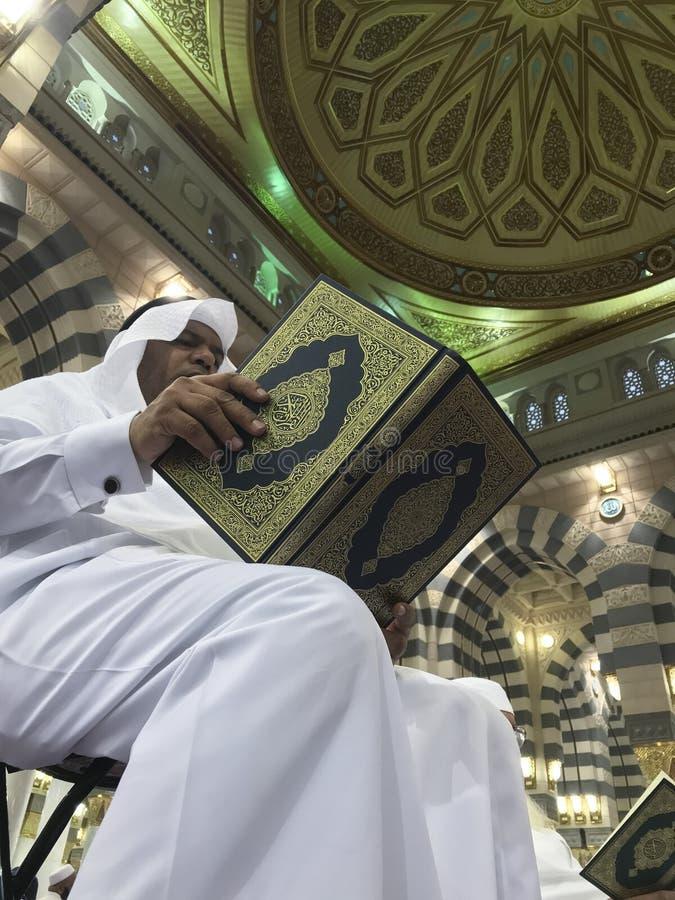 MEDINA-MAY 26日2019年:穆斯林在Madinah读古兰经并且祈祷里面Masjid Nabawi,沙特阿拉伯 Nabawi清真寺是第二 免版税库存照片