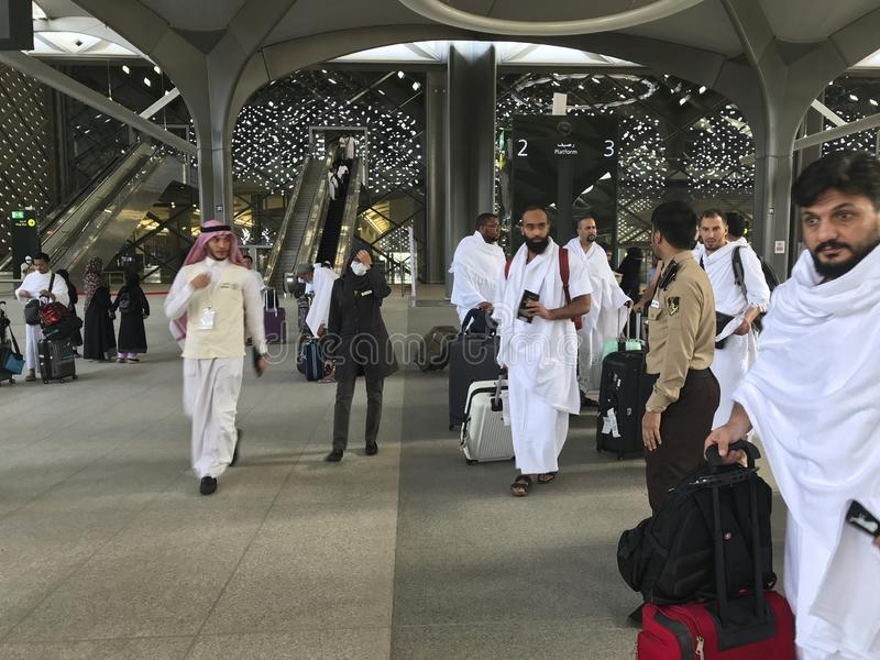MEDINA, SAUDI ARABIA - MAY 27, 2019 :  a group of men in white ihram clothes ready to embark train coaches at HSR Madinah station royalty free stock photo