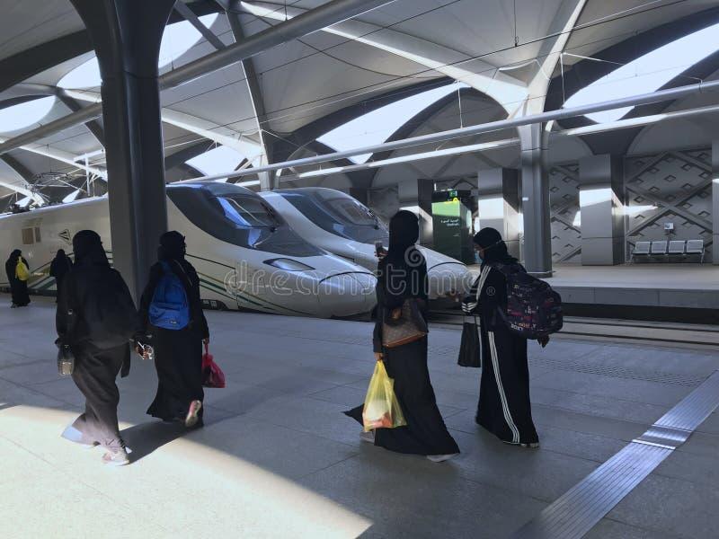 MEDINA, SAUDI-ARABIEN - 27. MAI 2019: eine Frauengruppe in den schwarzen abayas bereit, sich Zugzüge an Station HSR Madinah herei stockfotografie