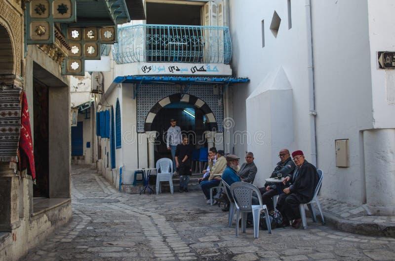 Medina van Sousse, oude mensen die en koffie op de straat babbelen drinken dichtbij koffie stock afbeeldingen