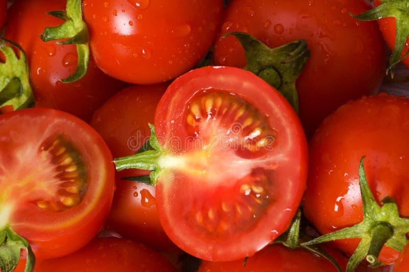 Medio corte y tomates enteros imagenes de archivo