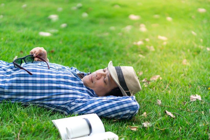 Medio hombre de la longitud que se relaja y que duerme en parque foto de archivo