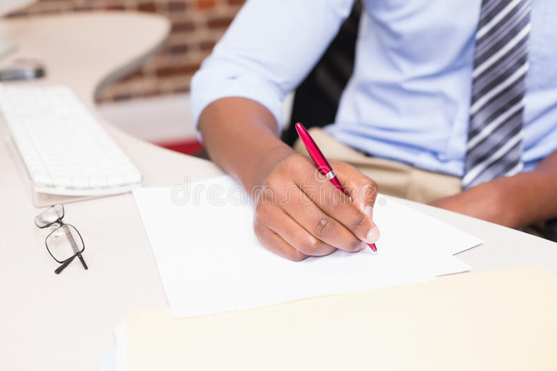 Medio hoofdstuk van zakenman het schrijven document bij bureau royalty-vrije stock fotografie