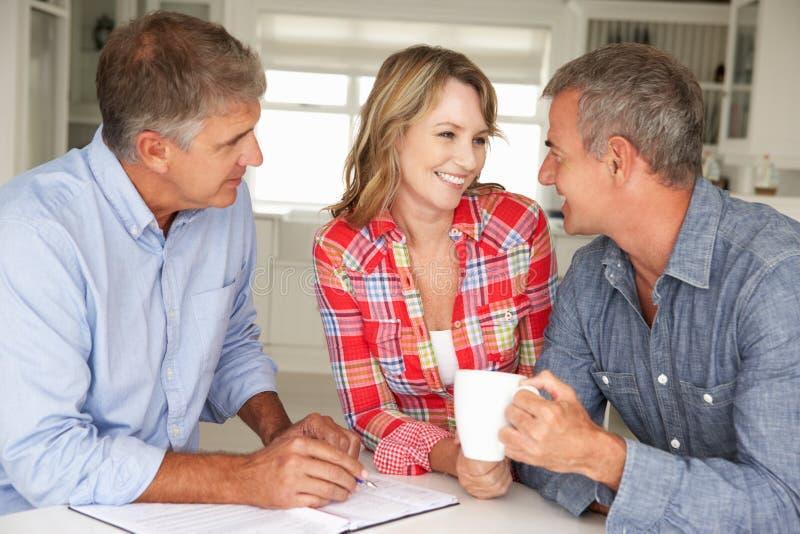 Medio leeftijdspaar met financiële adviseur thuis stock fotografie