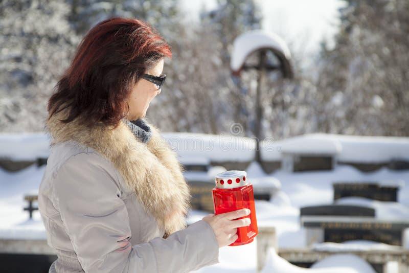 Medio oude vrouw met kaars op sneeuwbegraafplaats stock afbeelding